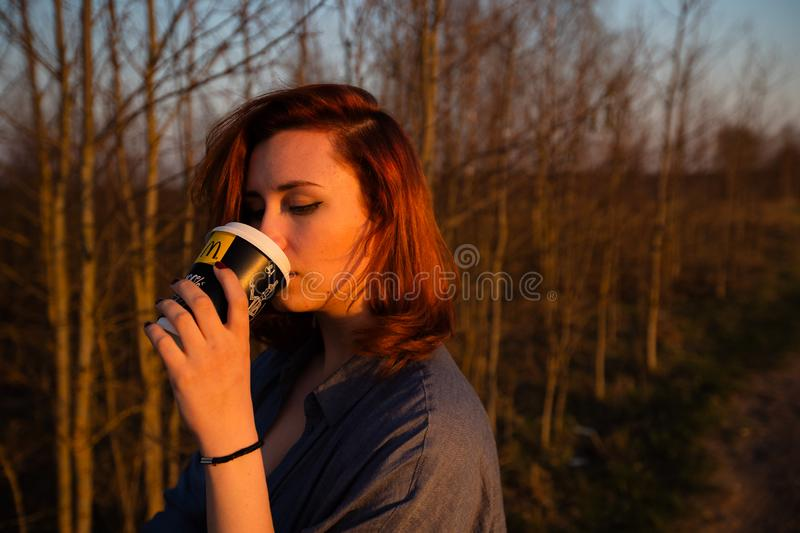 MARUPE, LATVIA - APRIL 22, 2019: Young woman drinking McDonalds coffee outdoors in a field during sunset royalty free stock image