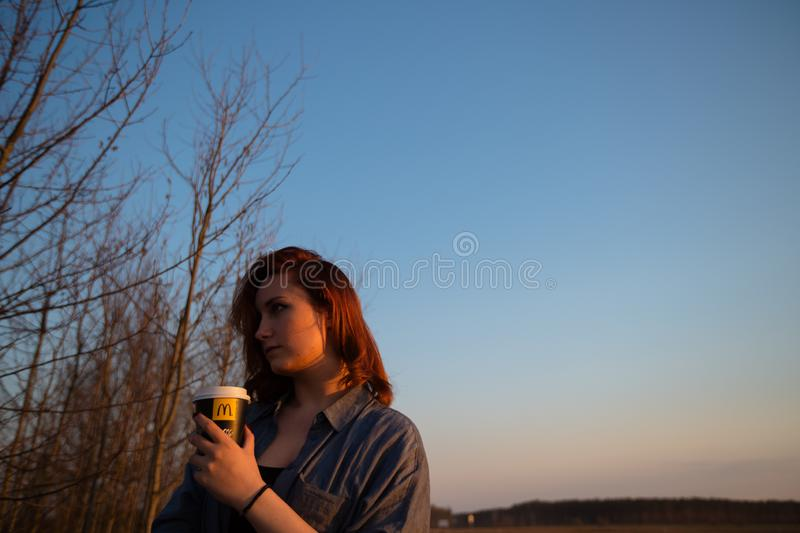 MARUPE, LATVIA - APRIL 22, 2019: Young woman drinking McDonalds coffee outdoors in a field during sunset stock photo