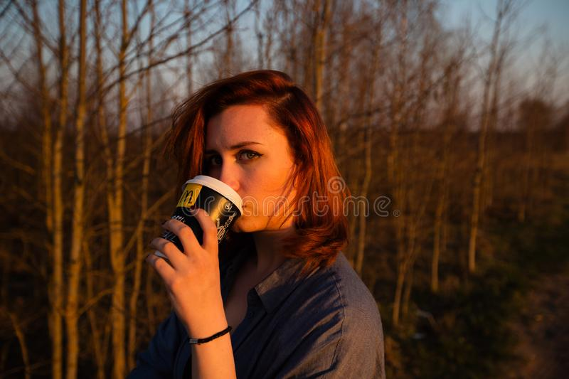 MARUPE, LATVIA - APRIL 22, 2019: Young woman drinking McDonalds coffee outdoors in a field during sunset stock photography