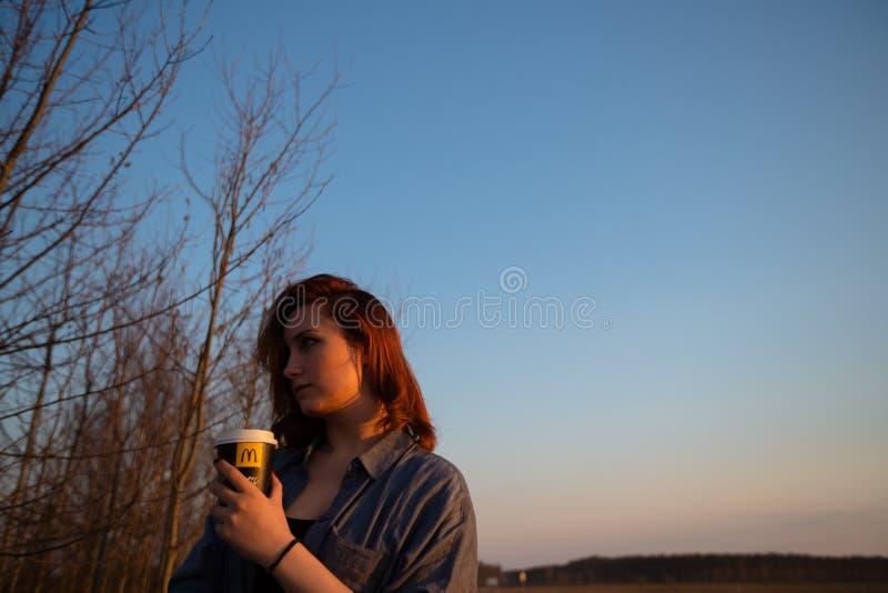 MARUPE, LETLAND - APRIL 22, 2019: Jonge vrouw die McDonalds-koffie in openlucht op een gebied drinken tijdens zonsondergang stock foto