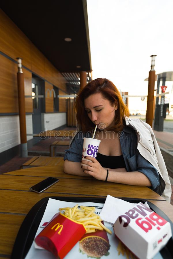 MARUPE, LETTONIE - 22 AVRIL 2019 : Jeune femme buvant du caf? de McDonalds dehors dans un domaine pendant le coucher du soleil photo stock