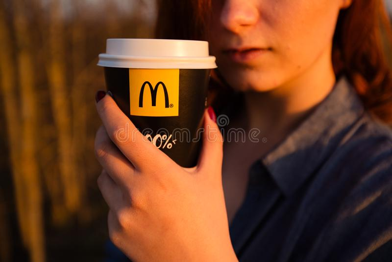 MARUPE, LETTONIE - 22 AVRIL 2019 : Jeune femme buvant du caf? de McDonalds dehors dans un domaine pendant le coucher du soleil image stock