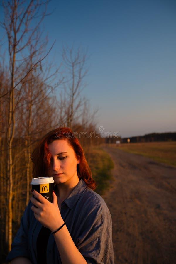 MARUPE, LETTONIE - 22 AVRIL 2019 : Jeune femme buvant du caf? de McDonalds dehors dans un domaine pendant le coucher du soleil images stock