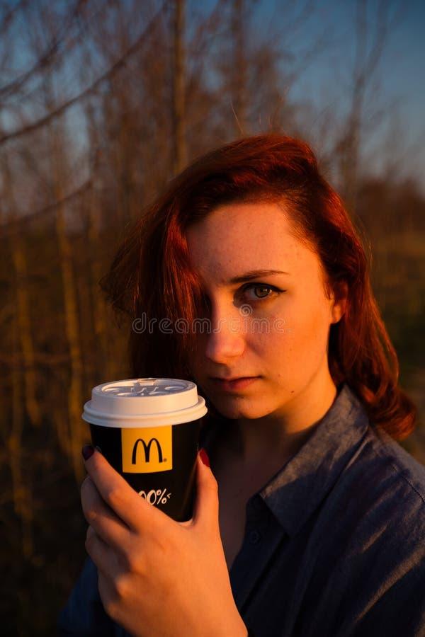 MARUPE, LETTONIE - 22 AVRIL 2019 : Jeune femme buvant du caf? de McDonalds dehors dans un domaine pendant le coucher du soleil photo libre de droits