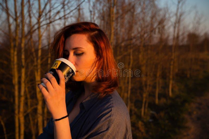 MARUPE, LETTONIE - 22 AVRIL 2019 : Jeune femme buvant du caf? de McDonalds dehors dans un domaine pendant le coucher du soleil image libre de droits