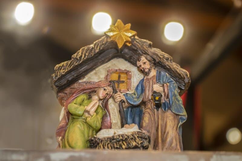 Mary e Joseph bíblicos olham para baixo no bebê Jesus no comedoiro em uma cena da natividade do Natal contra o fundo do bokeh imagens de stock royalty free