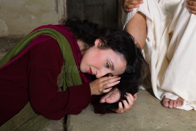 Mary Magdalene суша ноги Иисуса с ее волосами стоковые фото