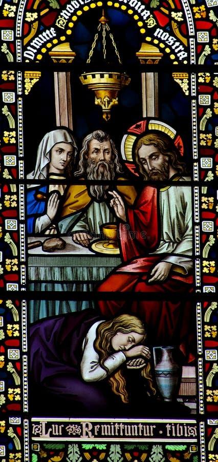 Mary Magdalene som tvättar foten av Jesus i målat glass arkivfoton