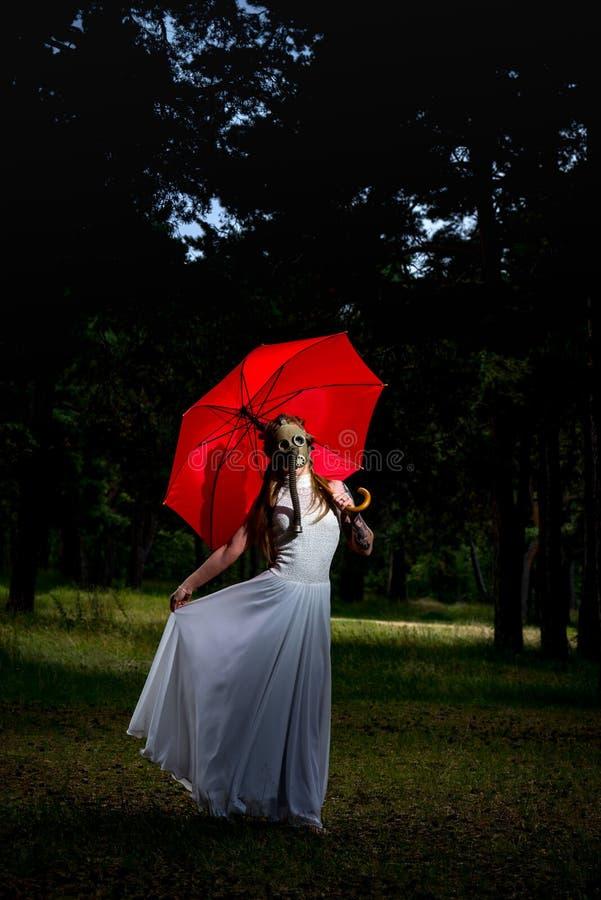 Mary Poppins, conceito moderno da forma Modelo fêmea branco caucasiano que está com máscara vermelha do guarda-chuva e de gás imagem de stock