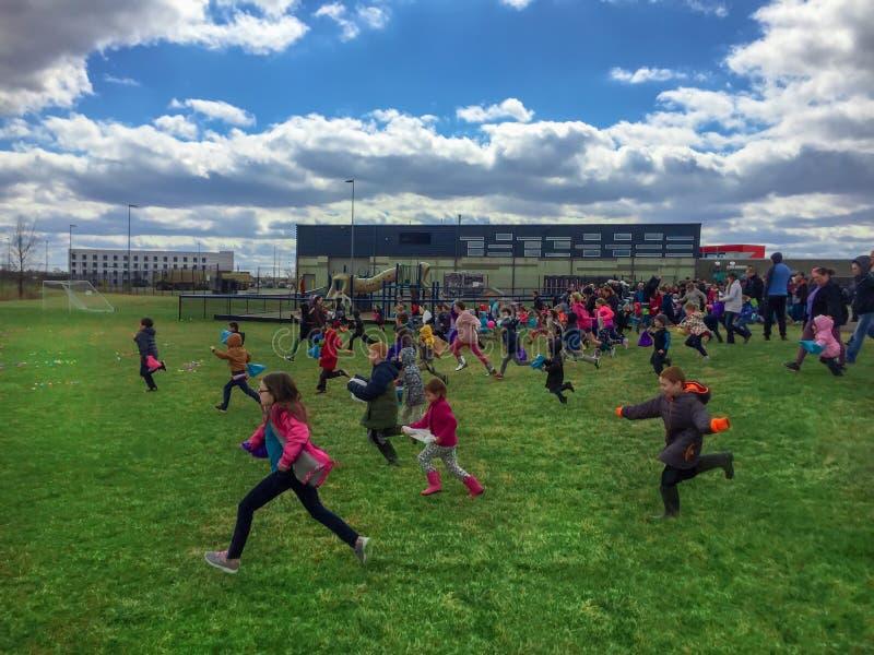 Marysville, OH/03 06 2018: Dzieci biega na wczesnym Easter jajka polowania wydarzeniu zbierać kolorowych Easter jajka obrazy stock