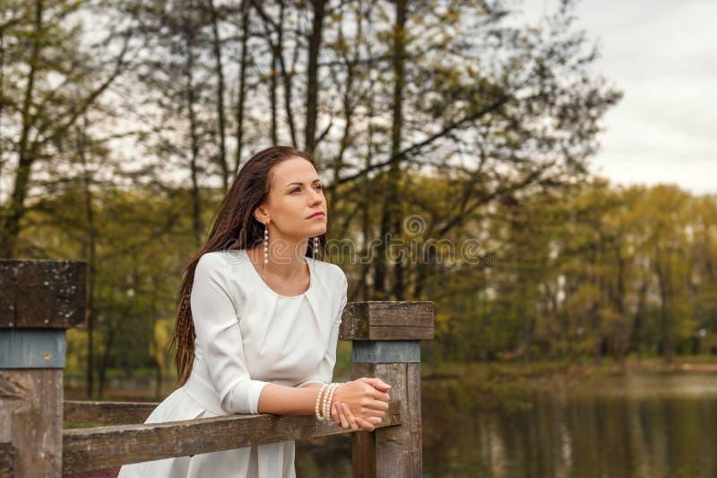 Marzący zadumanej młodej kobiety stoi opierać na poręczu drewniany most w biały smokingowy patrzeć naprzód fotografia royalty free