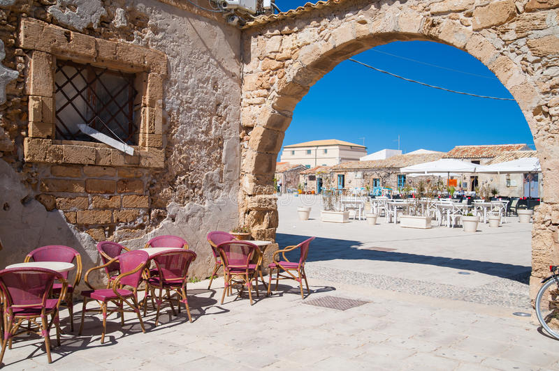 Marzamemi corners. Stone arch entrance to main square of the fishing village Marzamemi, South East Sicily, and some chairs of a bar royalty free stock images