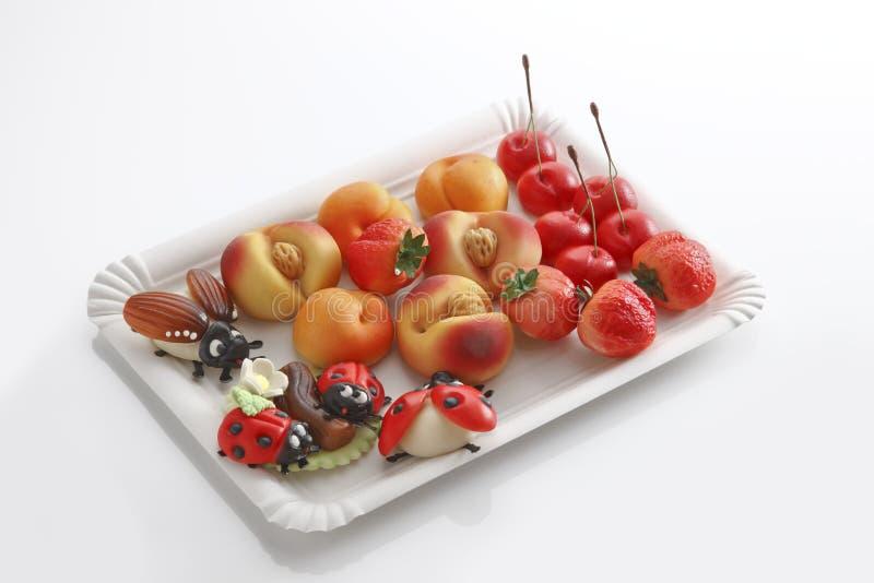 Marzipan, Marienkäfer, hört möglicherweise, Pfirsiche, Erdbeeren, Kirschen auf Pappteller ab stockfoto
