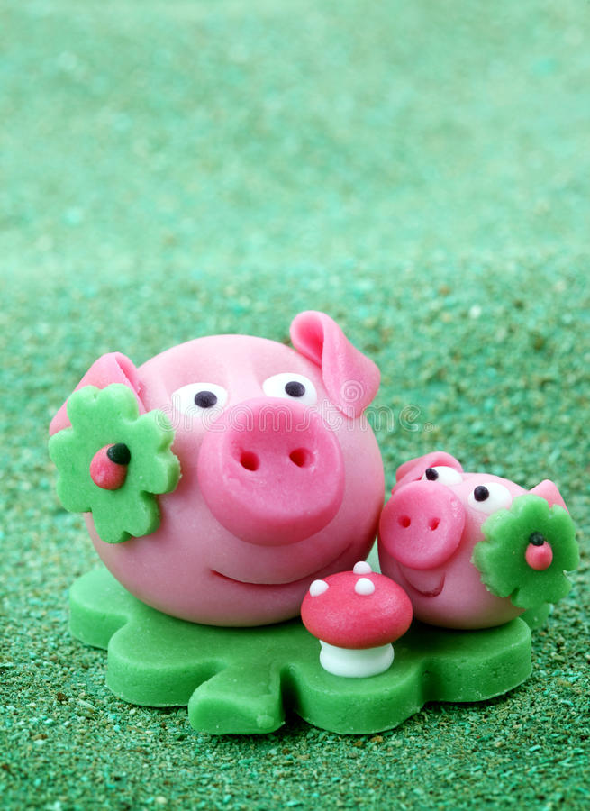 Marzipan pig with cloverleaf. And mushroom on green background stock image