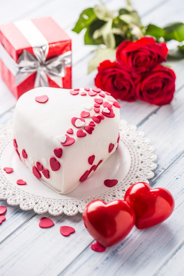 Marzipan white cake in the shape of a heart with red hearts. As the decoration bouquet of red roses a gift from the ribbon. royalty free stock images