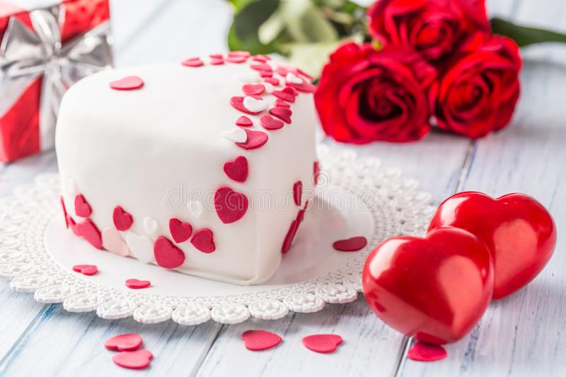 Marzipan white cake in the shape of a heart with red hearts. As the decoration bouquet of red roses a gift from the ribbon. royalty free stock photos