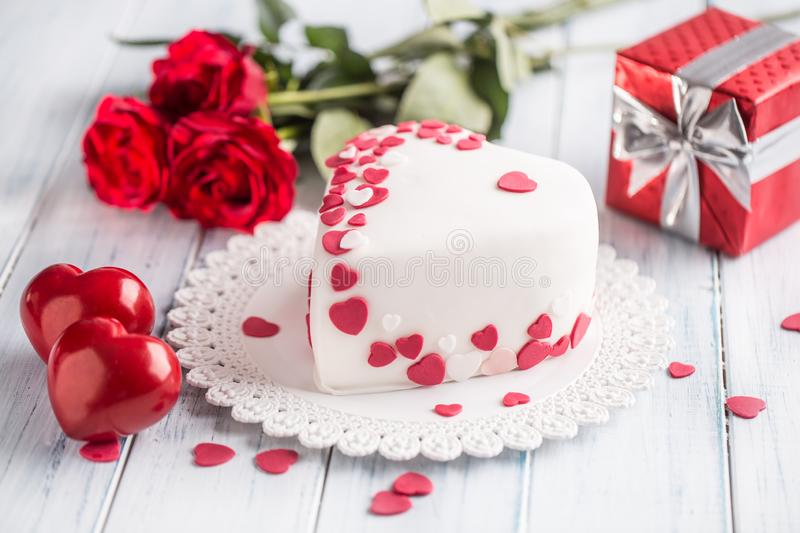 Marzipan white cake in the shape of a heart with red hearts. As the decoration bouquet of red roses a gift from the ribbon. royalty free stock photography