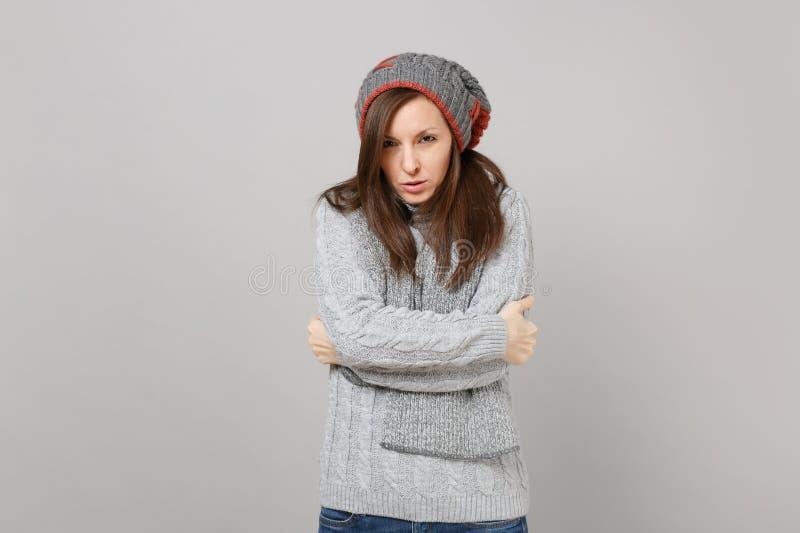 Marznięcie młoda kobieta w szarym pulowerze, kapeluszowy szalika mienie wręcza fałdowy odosobnionego na popielatym tle w studiu Z obraz royalty free