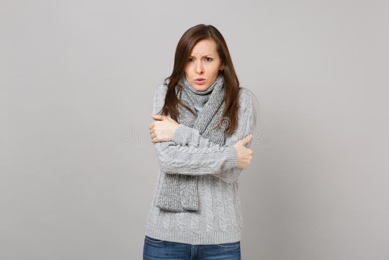 Marznięcie młoda kobieta w szarym pulowerze, szalika mienie wręcza fałdowy odosobnionego na popielatym ściennym tle w studiu Zdro zdjęcie stock