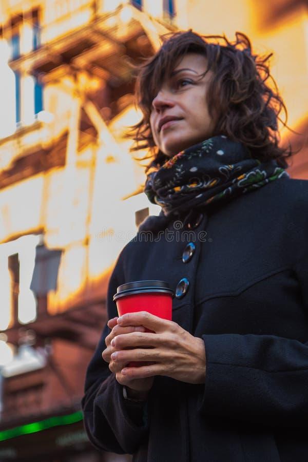 Marznięcie młoda dama w eleganckim czarnym żakiecie pije kawę zdjęcia royalty free