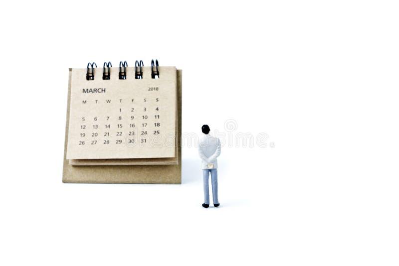 marzo Haga calendarios la hoja y al hombre plástico miniatura en el backgro blanco imágenes de archivo libres de regalías