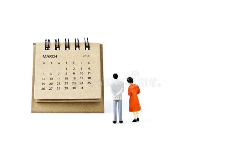 marzo Haga calendarios la hoja y hombre y mujer plásticos miniatura en whi imagenes de archivo