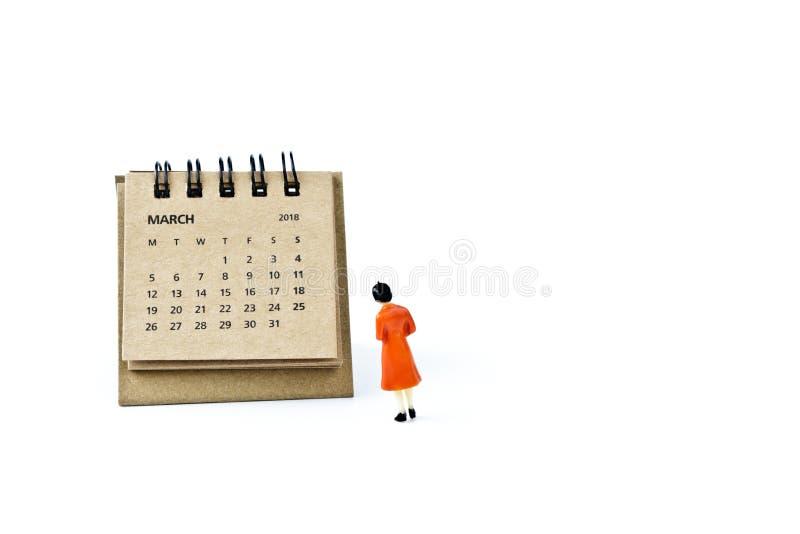 marzo Haga calendarios la hoja y a la mujer plástica miniatura en el backg blanco fotografía de archivo libre de regalías