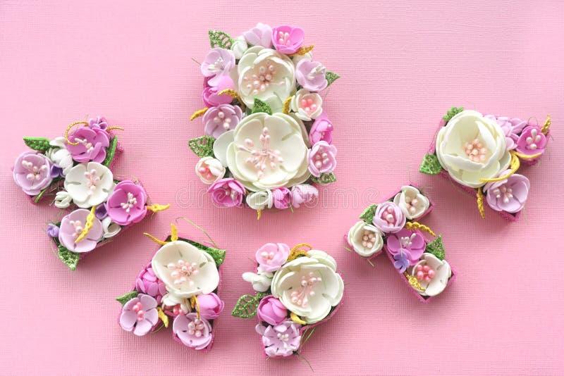 8 marzo iscrizione allineata con i fiori pastelli multicolori nelle lettere russe su un fondo rosa immagini stock
