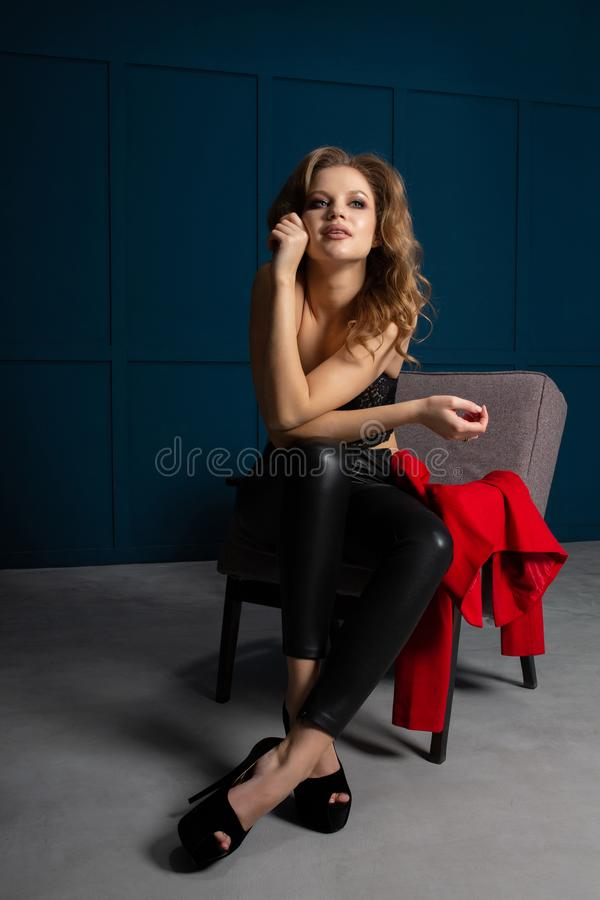 Marzyć blondynki damy jest ubranym koronkowych bluzki i skóry spodnia z luksusowym kędzierzawym włosy, pozuje przy studiiem zdjęcia stock