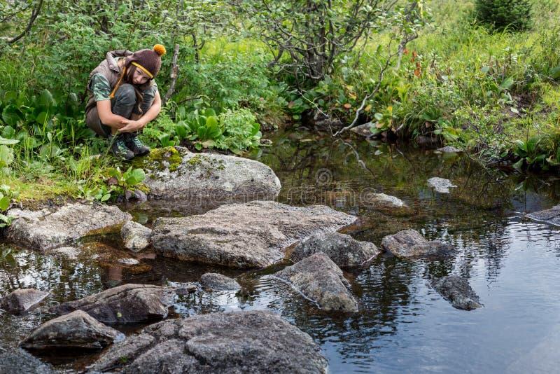 Marzyć dziewczyny obsiadanie na moscie z lasem i rzeką na tle Osamotniona smutna kobieta jeziorem piękna kobieta obraz royalty free