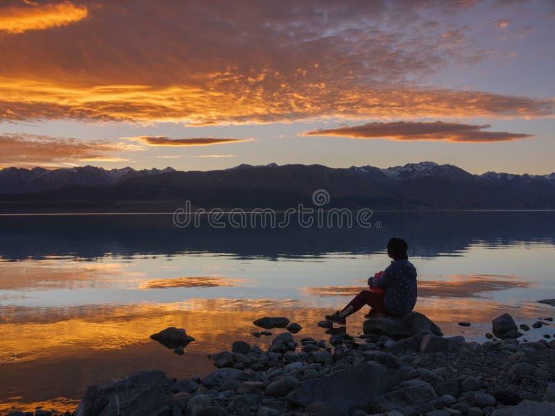 Marzycielka, sylwetka kobiety obsiadanie wzdłuż jeziora przy zmierzchem, ludzka siła, psychologii pojęcie obraz stock
