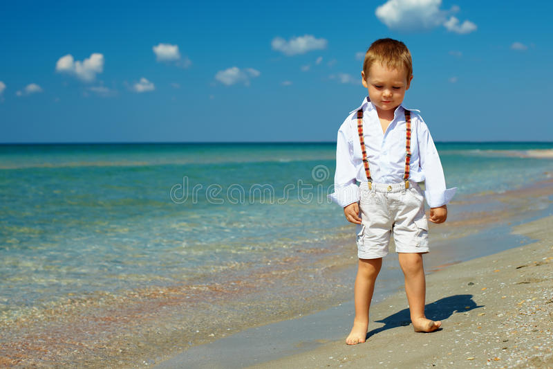 Marzycielscy chłopiec stojaki w kipieli na morzu wyrzucać na brzeg obrazy stock