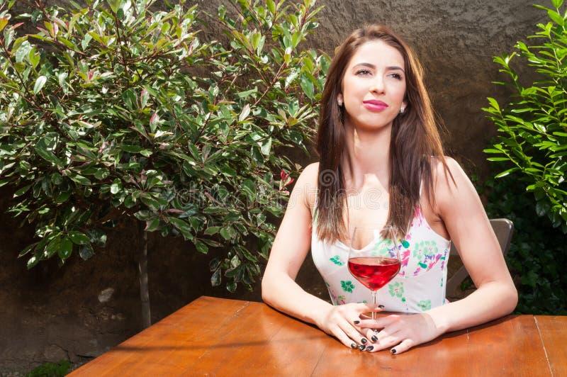 Marzycielska dziewczyna cieszy się szkło wino na tarasie zdjęcie stock