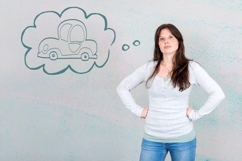 Marzycielska młoda kobieta życzy kupować nowego samochód symbolizującego samochodem wewnątrz obraz stock