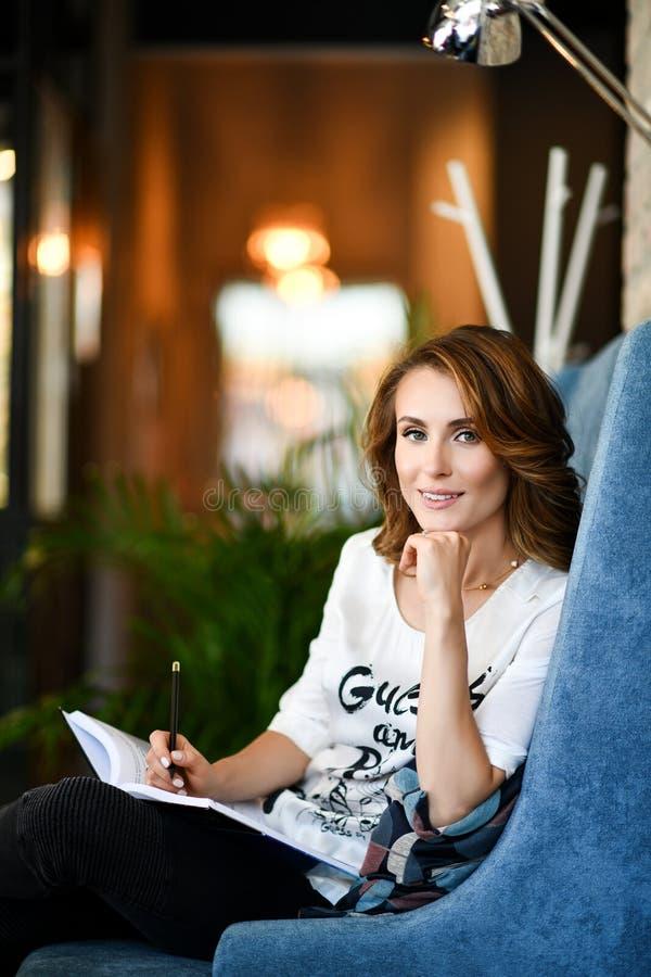 Marzycielska młoda piękna kobieta czyta książkę pisze planach na przyszłość i celach w jej dzienniczku, relaksuje w wygodnej jada fotografia royalty free