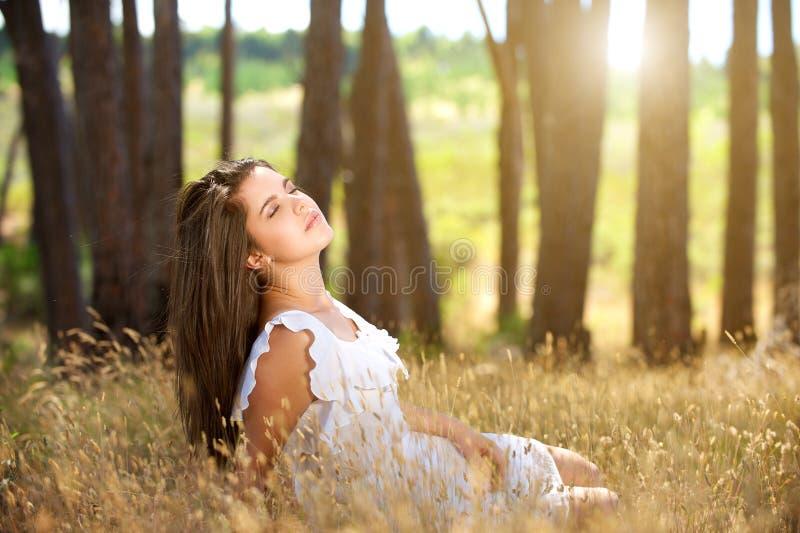 Marzycielski młodej kobiety obsiadanie w polu z światłem słonecznym w tle zdjęcie royalty free