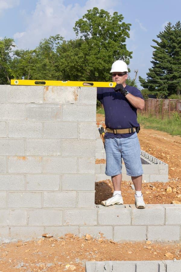 Masón con el bloque de cemento imagen de archivo libre de regalías