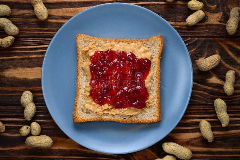 Masła orzechowego i galarety kanapka na drewnianym tle zdjęcie royalty free