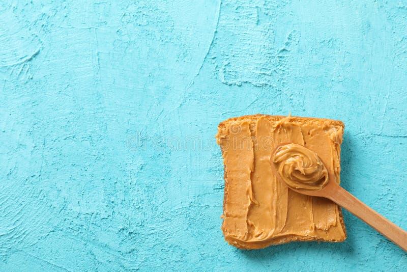 Masło orzechowe łyżka na koloru tle i kanapka, przestrzeń dla teksta obrazy stock