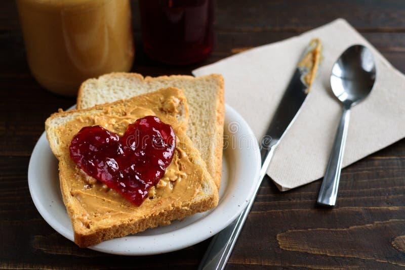 Masło orzechowe i serce kształtująca galaretowa kanapka obrazy stock