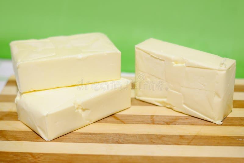 Masło wewnątrz brykietuje na ciapanie desce obraz royalty free