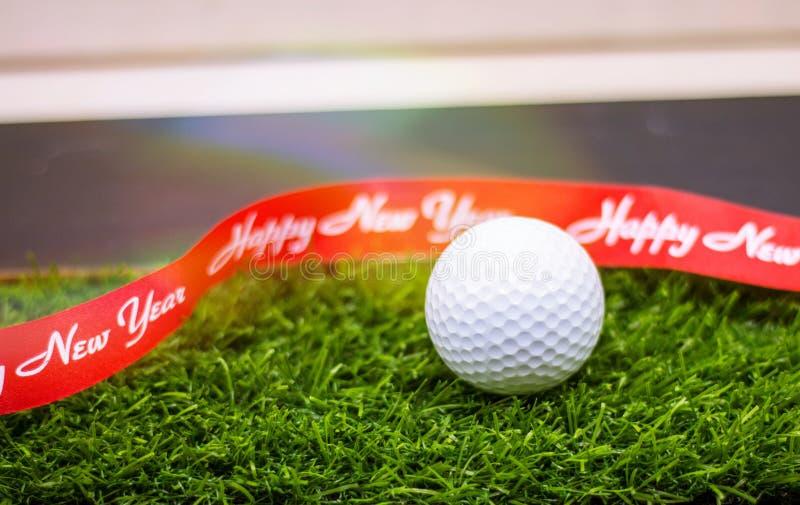 Mas del ` de la pelota de golf el feliz X y la Feliz Año Nuevo firman en hierba verde fotos de archivo libres de regalías