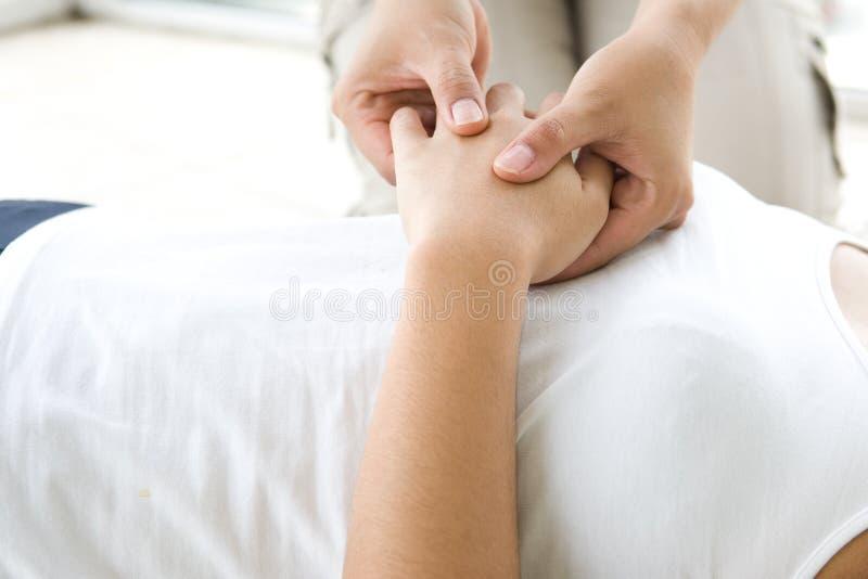 masaż pacjenta poprzez ręka obraz stock