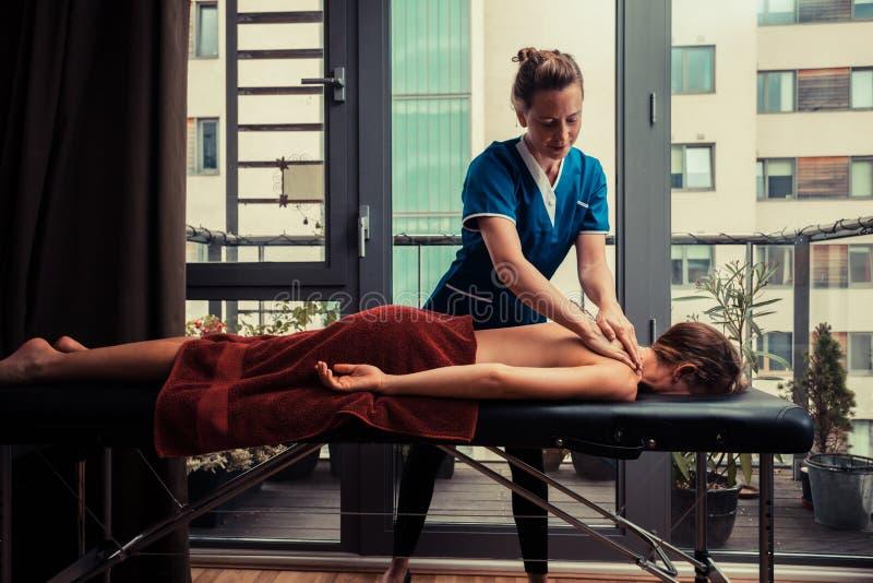 Masażu terapeuta częstowania pacjent w domu zdjęcia stock