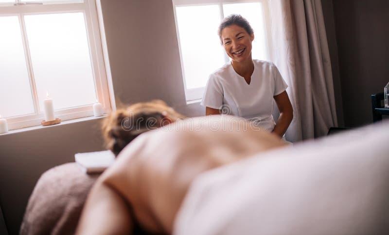 Masażysta opowiada z żeńskim lying on the beach na masażu stole w zdroju salonie zdjęcie stock
