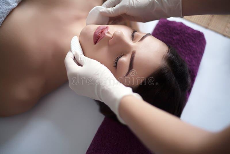 Masażysta robi masażowi głowa dorosła kobieta w zdroju salonie zdjęcia stock