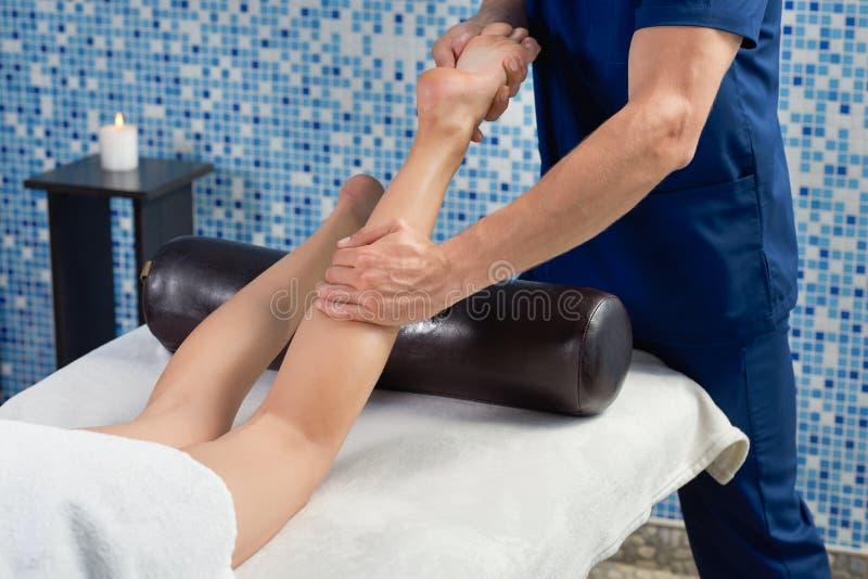 Masażysty masowania łydkowy mięsień i stopa kobieta w zdroju zdjęcia stock