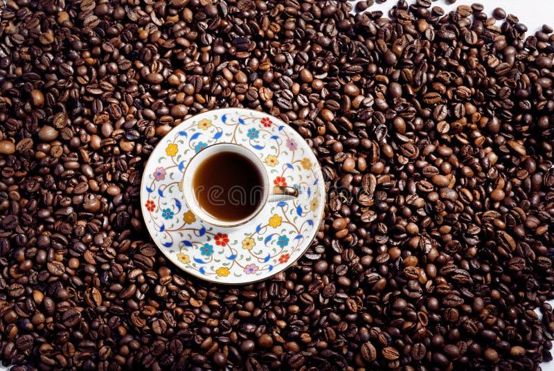 Masa brillante de los granos de café del arabica y de la pequeña placa con la taza de café en estilo oriental Opinión superior so fotos de archivo