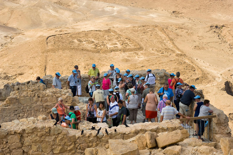 Masada in Israel. MASADA, ISRAEL - OCT 14, 2014: Tourists on top of the rock Masada in Israel, with a Roman camp on the background royalty free stock image