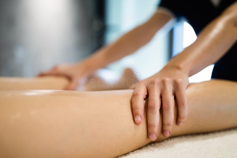 Masaging πόδια μασέρ του προσώπου στο μασάζ στοκ εικόνα